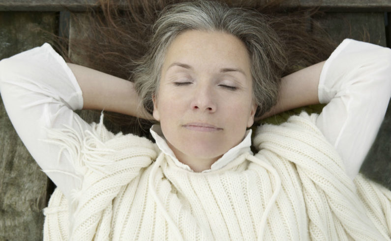Older-woman-laying-on-wooden-dock-FINAL